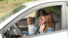 Mother talking on the phone behind the wheel of a car, sitting next to a child.