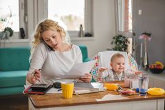 Mother talking on smart phone at home office Royalty Free Stock Photo