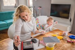 Mother talking on smart phone at home office Royalty Free Stock Images