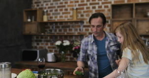 Mother Talking With Son Using Tablet Computer While Father With Daughter Cooking Food In Kitchen, Happy Family Spending stock footage