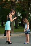 Mother talking to naughty girl on a street in park. At dusk Royalty Free Stock Image