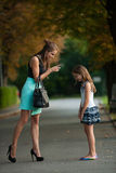 Mother talking to naughty girl on a street in park Stock Photos
