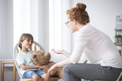 Mother talking to polite son. Mother talking to her polite, young son hugging a teddy bear Stock Photo