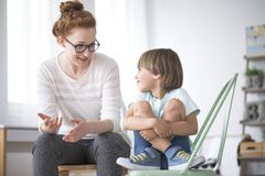 Mother talking to smiling son. Mother talking to her smiling son sitting on green chair about school stock photos