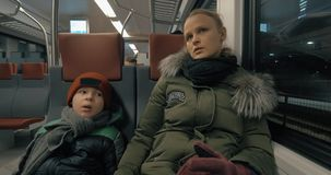 Mother and child having a ride in suburban train. Mother talking to son while they traveling by suburban train in winter evening stock footage
