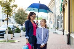 Mother talks with her daughter for ten years on her way to school. Urban background, under an umbrella. Royalty Free Stock Photography