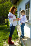 Mother with te son in Ukrainian national clothes play near the h Royalty Free Stock Photo