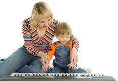 Mother teach baby play piano. Over white background royalty free stock image
