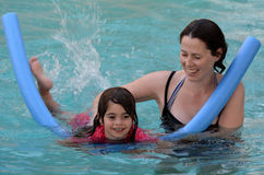 Mother teach her child to swim. Young mother teach her child (girl age 04) to swim with pool noodle in a swimming pool stock photo