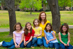 Mother teacher with daughter pupils in playground park royalty free stock image