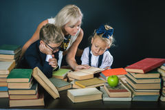 Mother or teacher helping for school kids doing homework, reading Stock Image