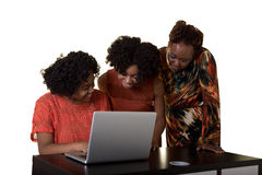 A mother or teacher looking at a computer with 2 teenagers Royalty Free Stock Photos