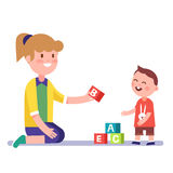 Mother or teacher teaching a child alphabet. Mother or kindergarten teacher teaching a child alphabet with letter wooden bricks blocks. Modern flat style vector Stock Photo
