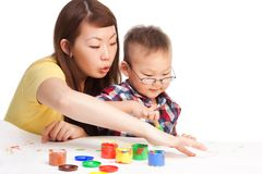 Mother teaches. Little her Chinese boy how to paint royalty free stock image