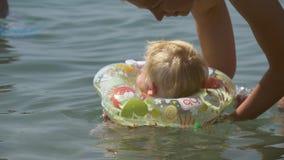 Mother teaches baby to swim stock video
