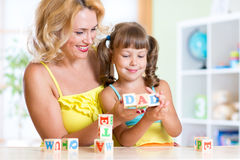 Mother teaches child letters and words playing Stock Images