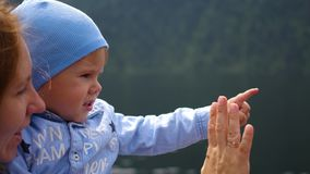 The mother teaches the child to gesture goodbye stock video footage