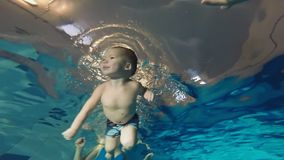 Mother teaches the child to swim under water. Mother teaches the child to swim under water stock video