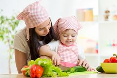 Mother teaches daughter knife cut cucumber. Cute mother teaches daughter knife cutting cucumber royalty free stock photos