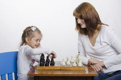 Mother teaches daughter to play chess Stock Photos