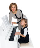 Mother teaches daughter to play the piano Stock Photo