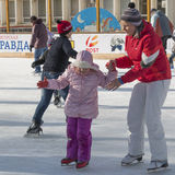 Mother teaches daughter to stand on skates Royalty Free Stock Photo