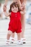 Mother teaches daughter to walk Stock Photos