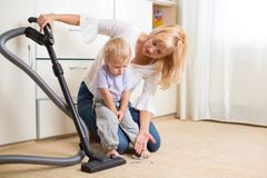 Mother teaches her child son room cleaning. With vacuun cleaner royalty free stock images