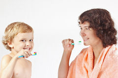 Mother teaches her child to brush their teeth Stock Photo