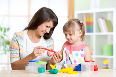 Mother teaches her child to play with colorful Royalty Free Stock Image