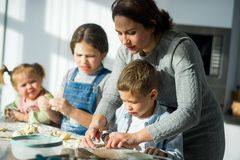 Mother teaches her children how to cook. Two girls and the boy very much try. Their faces in flour, dough has stuck to hands Royalty Free Stock Photos