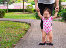 Mother teaches her happy young daughter how to walk on her own stock photo