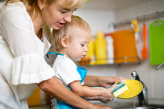 Mother teaches her little child son to wash-up Stock Photography