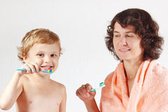 Mother teaches her little child to brush teeth Stock Photo