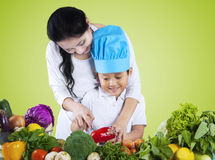 Mother teaches her son to cut vegetables Stock Photography