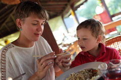 Mother teaches her son to use chopsticks. In the restaurant Stock Photography