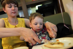 Mother teaches her son to use cutlery Royalty Free Stock Photo