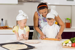 Mother Teaches How to Bake to Kids Royalty Free Stock Images