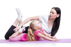 Mother teaches kid girl exercising showing by Royalty Free Stock Photos