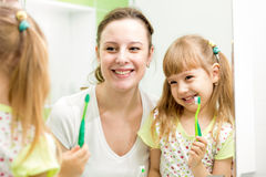 Mother teaches kid girl to brush teeth Stock Images