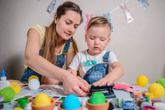 Mother teaches kid to do craft items Stock Images