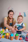 Mother teaches kid to do craft items Stock Photography