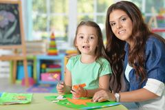 Mother teaches kid to do craft items. Mother teaches her cute little daughter to do craft items stock photo