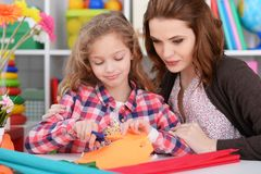 Mother teaches kid to do craft items stock image