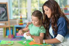 Mother teaches kid to do craft items. Mother teaches her cute little daughter to do craft items royalty free stock photos