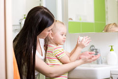 Mother teaches kid washing hands in bathroom Stock Images