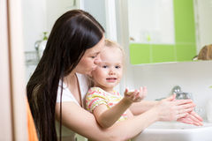 Mother teaches kid washing hands in bathroom Stock Image