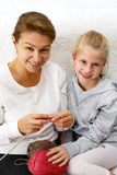 Mother teaches little daughter to knit. Stock Images