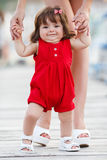 Mother teaches little daughter to walk alone Royalty Free Stock Images