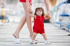 Mother teaches little daughter to walk alone Stock Image